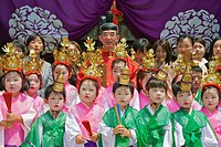 A group portrait of costumed children with a priest and mothers behind