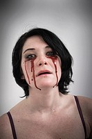 Woman with blood dripping from under her eyes