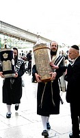 Orthodox Jewish men holding Torah scroll books by the Wailing wall in the old city of Jerusalem.