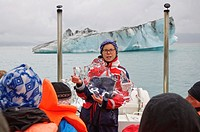 A guide explains glacial ice onboard a tour of Glacier Lagoon, Iceland