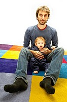 Father hold his 10 months old baby while on a multi coloured carpet