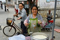 Street vendor selling fresh curd Douhua with syrup offering treat in Fuli China