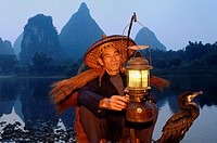 Cormorant fisherman with lamp and bird on bamboo raft at dawn on the shore of the Li river Yangshuo China