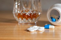 Close up of medical tablets and capsules with alcoholic drink in the background