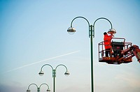 a workman working at height on a high access platform maintaining a street lamp light UK