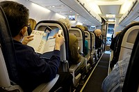 Man reading Magazine on Plane, Sunwing Airlines, Toronto, Canada