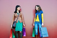 Two young women outdoors with shopping bags