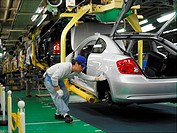 Factory workers producing the hybrid Toyota Prius cars, work on the assembly line at the Toyota City factory in Japan. Here a Scion TC is being inspec...