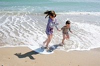 Boy and girl playing in the beach hand in hand, El Saler beach, Albufera de Valencia Nature reserve, Valencia, Spain