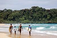 Surfers walking along the sea at Wizard Beach First Beach on Isla Bastimentos, Bocas del Toro, Panama
