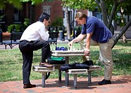 Men playing chess during lunch break in an outdoor park table - Washington, DC
