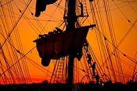 Sailors Take Down the Sails on an Old Ship at Sunset
