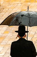 An orthodox Jewish man walks in the rain to pray at the Western Wall Wailing Wall, the old city, Jerusalem, Israel