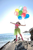 little girl jumping with joy holding balloons while at the ocean