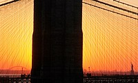 New York City, the Liberty Statue seen in the distance, at dusk, through the Manhattan Bridge