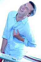 Man experiencing pain in his chest at his work office  This may be due to angina or a heart attack