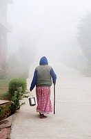 Woman with a walking stick on a misty path, Ma Dham Ashram for widows, Vrindavan, Uttar Pradesh, India