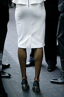 business woman in white skirt and high heels with business men.