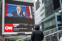 Passer-by gather in Times Square in New York on Monday, January 21, 2013 to watch the inauguration of Barack Obama for his second term as the 44th Pre...