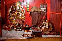 India, Rishikesh  Hindu Priest Sitting in a Shrine to Ganesh