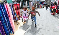 London, England, UK. Young black boy and girl running through street market in the East End.