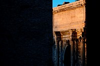An ancient roman arch located in the imperial fora photographed at sunrise dawn under warm morning sunlight between two roman walls  The sunlight illu...