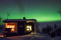 Cottage with northern light, aurora borealis in background in winter time at Riksgränsen in swedish lapland.