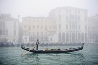 A Gondola sails along the Grand canal of Venice covered with thick fog, Italy.