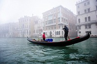 A Gondola sailing along the Grand canal of Venice covered with thick fog, Italy.