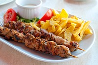 Chicken brochettes with chips and salad. Close view.