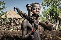 Portrait of a young mursi man holding a kalashnikov, Omo valley, Ethiopia.