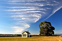 Farm house, tree and clouds, South Island, New Zealand.