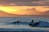 Surfersat sunset, The Pass, Byron Bay, New South Wales, Australia.