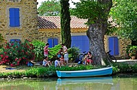 cyclists resting beside the Canal du Midi at Le Somail, Aude Department, France.