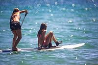 Girls on surfboard paddling in the Mediterranean Sea, Benicassim, Castellon province, Comunidad Valenciana, Spain