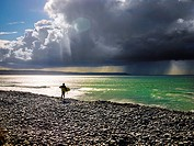 Surfer stood on a pebble beach looking out to sea with a rainstorm in the distance. Cornborough Range, Abbotsham, North Devon, England.