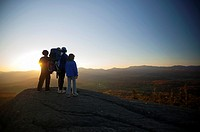Family watching sunset on top of The Pinnacle, Stowe, Vermont, USA.