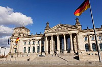 The Reichstag German Parlament building with German and EU flags streaming in the wind outside in Berlin, Germany.