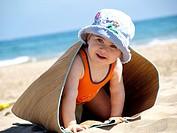 Small girl playing on the beach, Tarragona, Catalonia, Spain.