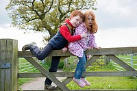 Brother and sister on a gate in the countryside.