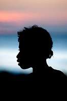 Silhouette of girl at sunset by sea at Warmandi in West Papua in Indonesia.