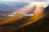 Sarek national park with with the Laitaure delta and mount Namatj in autumn season and the sun breaking through the clouds in Swedish lapland, Sweden.
