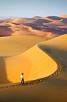 Woman in the sand dunes of the empty quarter desert. United Arab Emirates, UAE, Abu Dhabi, Liwa Oasis, Moreeb Hill, Tal Mireb. Model Released.