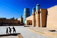Children playing near the Kuhna Ark fortress and the unfinished minaret Kalta Minor. Uzbekistan, Khorezm, Khiva, Itchan Kala (inner town).