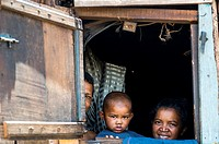 A Malagasy family peeking out their house window in a village near Antananarivo.