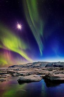 Moon and Aurora Borealis. Northern lights with the moon illuminating the skies and icebergs at the Jokulsarlon Glacial lagoon, Iceland.