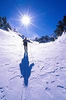 Backcountry skier crossing wind blown snow near Treasure Lakes, John Muir Wilderness, California USA.
