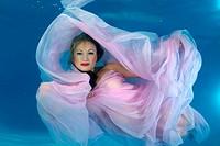 Woman presenting underwater fashion in pool, Odessa, Ukraine, Eastern Europe.