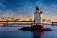 The Tarrytown Lighthouse also know as the Sleepy Hollow Light and Kingsland Point Light during sunset with the Tappan Zee Bridge in the background. Ta...