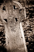 Close up of old tombstone with cross in graveyard, Sweden.